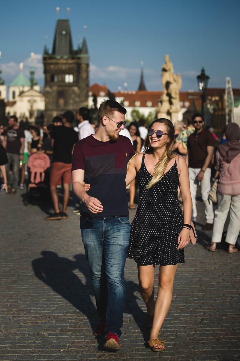 Para zakochanych idzie roześmiana po Moście Karola w Pradze w Czechach