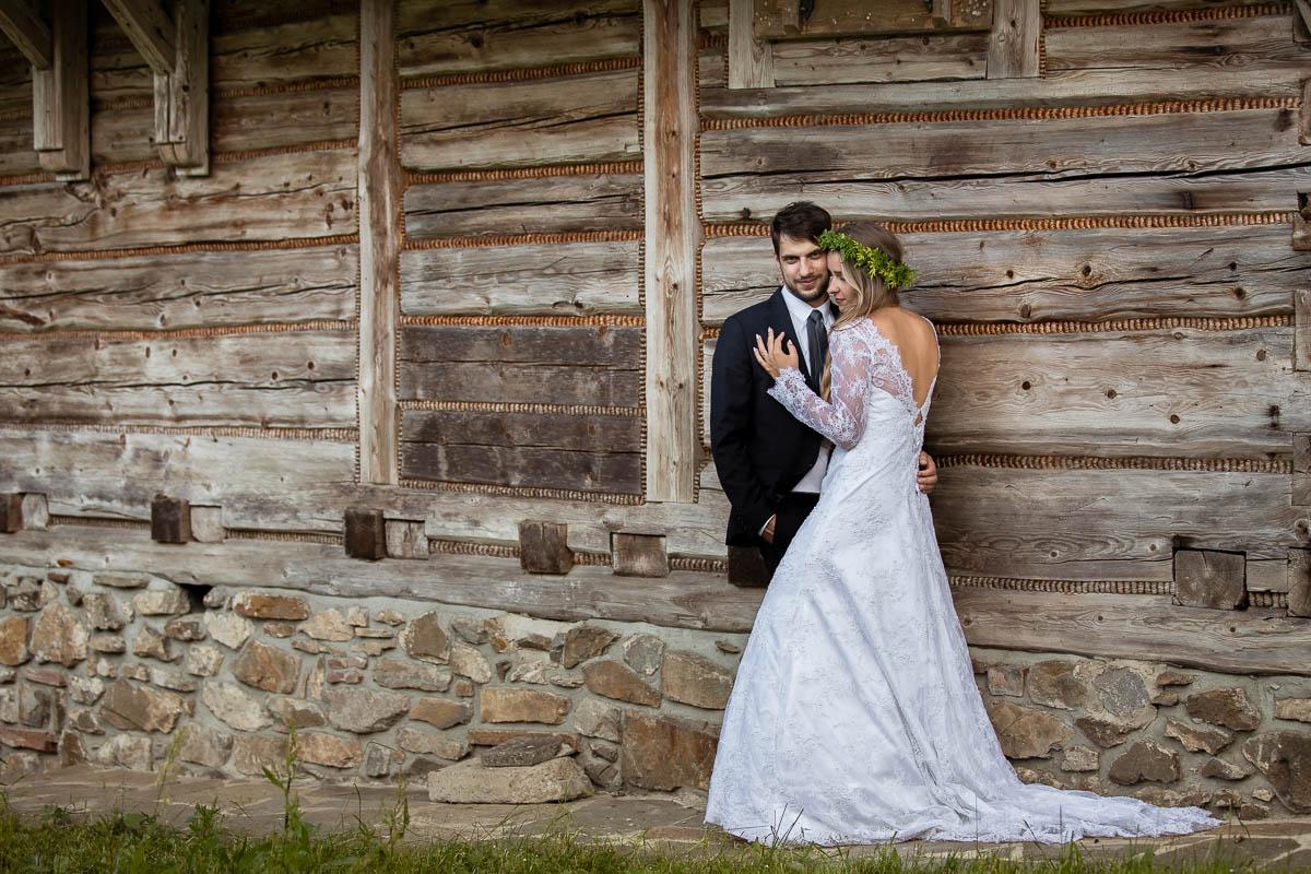 Pani Młoda w sukni ślubnej z długim rękawem stoi wtulona w Pana Młodego na tle starej chaty