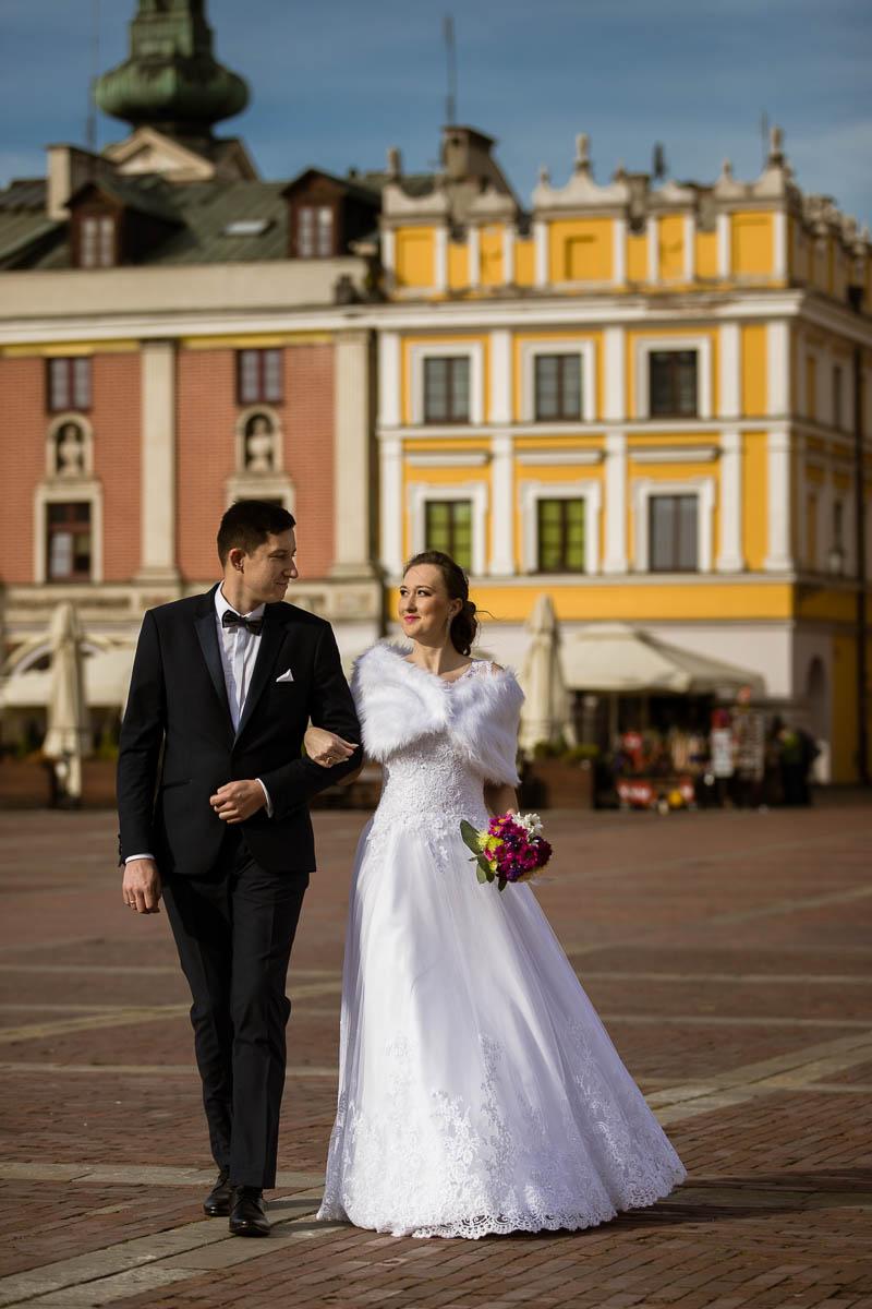 Pani Młoda spaceruje w sukni ślubnej z bolerkiem po Rynku w Zamościu trzymając pod rękę Pana Młodego